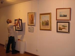 José Luis Risoto ,Comisario de la exposición, ordenando los cuadros